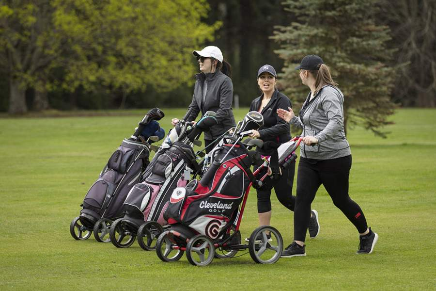 Three women holding the Golf Bag on the course, wearing caps, talking while walking