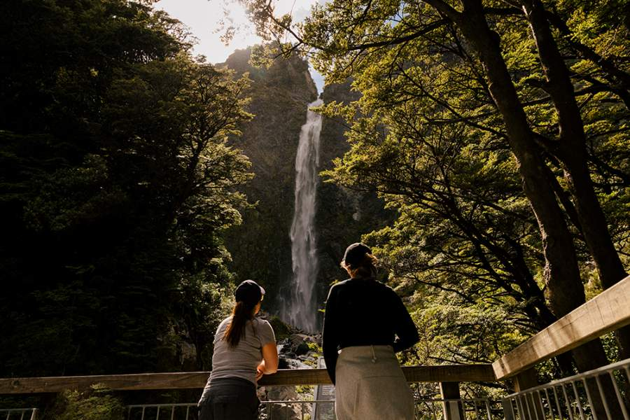 Two girls looking at the waterfall from the bridge, trees around them